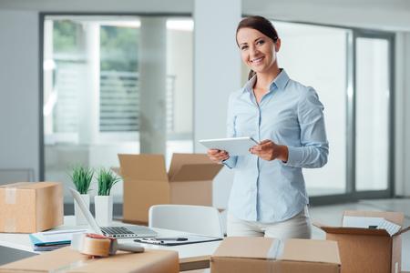 Confiado mujer de negocios sonriente que se mueve en su nueva oficina, que está desempacando cajas y el uso de una tableta digital