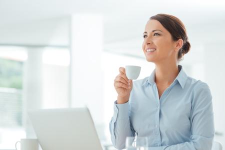Atraktivní usmívající se obchodní žena, sedící v kanceláři, držící šálek kávy, ona je relaxační a hledá dál