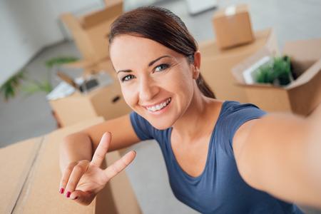 simbolo de la paz: Mujer alegre que toma un autorretrato en su nueva casa, ella está sonriendo a la cámara y haciendo un signo V