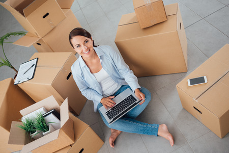 young woman sitting: Beautiful woman moving in her new house and unpacking, she is sitting on the floor surrounded by boxes, using a laptop and smiling at camera