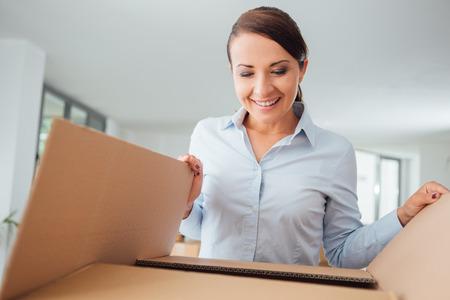 Glückliche überzeugte Frau Auspacken und der Umzug in ihr neues Büro, sie ist die Eröffnung einer Kartonschachtel und schauen hinein Standard-Bild
