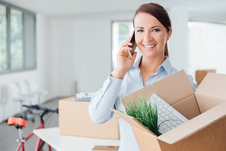 Krásná usmívající se žena pohybuje v nové kanceláři, mluví na telefonu a drží otevřenou krabici Reklamní fotografie
