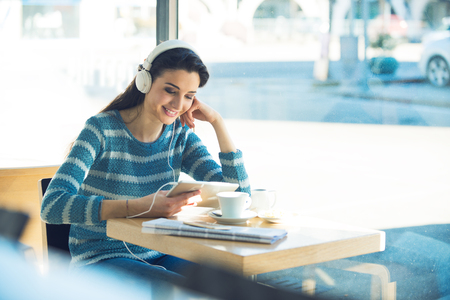 Smiling young woman at the cafe with headphones listening to music and using a tablet