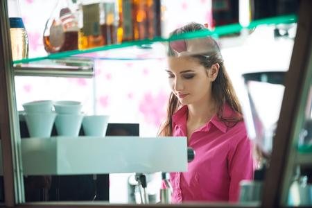 woman bar: Female barista making coffee with an espresso coffee machine