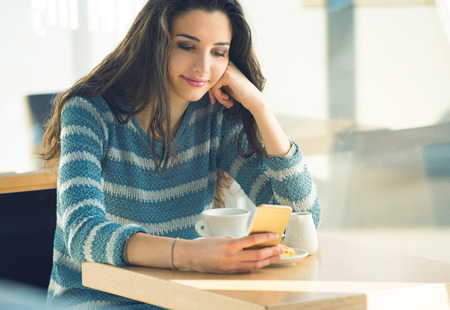 woman bar: Confident woman sitting at bar table and texting with her mobile phone
