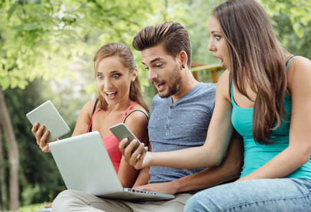young friends: Happy students at the park relaxing on a bench and using a laptop, a digital tablet and a smart phone Stock Photo