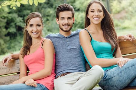 gente sentada: Adolescentes que se relajan en la sonrisa del parque durante un día de verano, que están sentados en un banco de madera y mirando a la cámara Foto de archivo