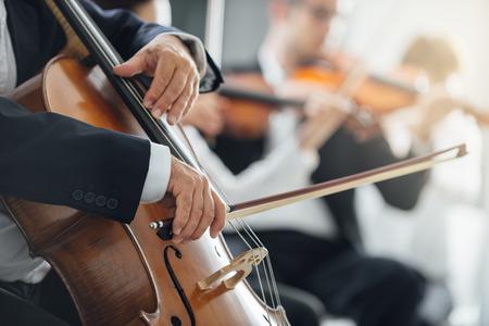 orquesta: Sección de cuerdas de la música clásica rendimiento orquesta sinfónica, el violonchelista jugar en primer plano, las manos se cierran para arriba