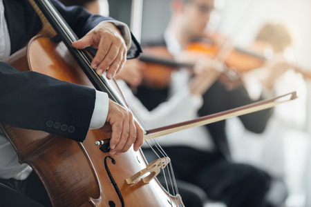 symphonic: String section of classical music symphony orchestra performing, cellist playing on foreground, hands close up Stock Photo