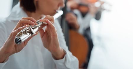 unrecognizable person: Professional female flute player performing with classical music symphony orchestra, unrecognizable person
