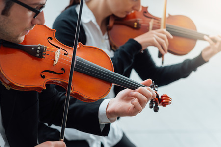 classical music: Two violinists performing together hands close up, classical music concert