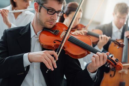 Clásica sinfonía de música sección de cuerdas de orquesta rendimiento, violinista masculino jugando en primer plano, la música y el trabajo en equipo concepto