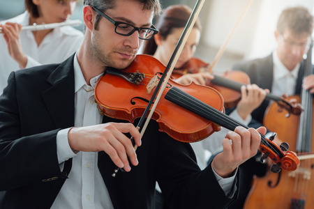 Classical music symphony orchestra string section performing, male violinist playing on foreground, music and teamwork concept