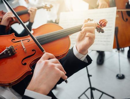 orquesta clasica: Violinista Confiado tocando su instrumento y la lectura de una hoja de música, clásica orquesta sinfónica de música se realiza en fondo
