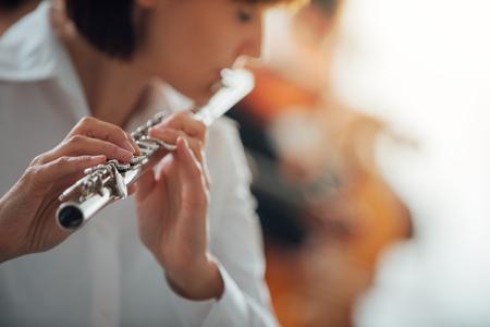 orquesta: Flautista de sexo femenino profesional tocando con la orquesta sinfónica clásica música, persona irreconocible