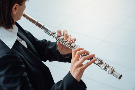 soloist: Elegant woman playing a transverse flute, classical music professional