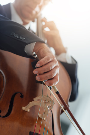 classical music: Professional male cellist playing his cello, classical music solo performance