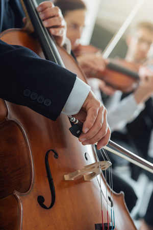 cellist: String section of classical music symphony orchestra performing, cellist playing on foreground, hands close up Stock Photo
