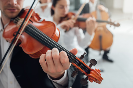orchestra: Classical music symphony orchestra string section performing, male violinist playing on foreground, music and teamwork concept