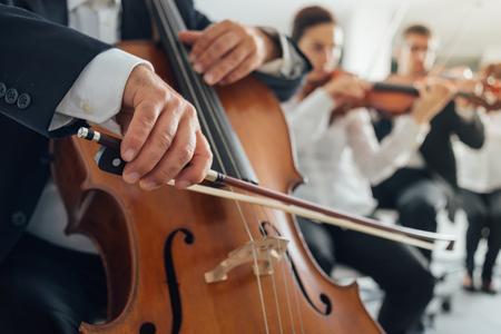 handen Professional cello speler close-up, hij presteert met strijkers van het symfonieorkest Stockfoto