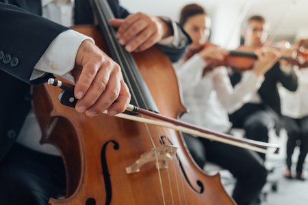 Professional cello player's hands close up, he is performing with string section of the symphony orchestra