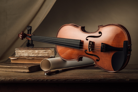 Old violin with music sheet rolls and old books on a wooden table, still life Imagens