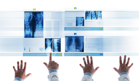 medical records: Professional medical team examining patients medical records and x-ray on touch screen slides, a doctor is touching an icon and scrolling