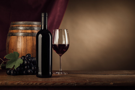 Red wine tasting with bottle, wineglass, barrel and grape on the cellar wooden table, red drape on background, still life