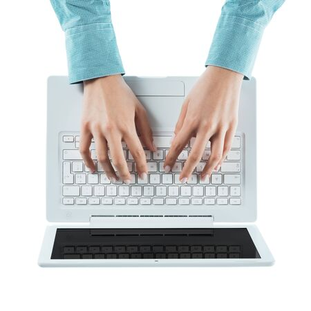 Business woman typing on a laptop keyboard on white background, top view, hands close up