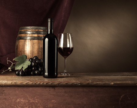 red cloth: Red wine tasting with bottle, wineglass, barrel and grape on the cellar wooden table, red drape on background, still life