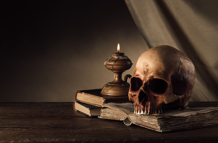 Cráneo humano, vela encendida y abierto libro antiguo en una vieja mesa de madera, el conocimiento y la alfabetización concepto