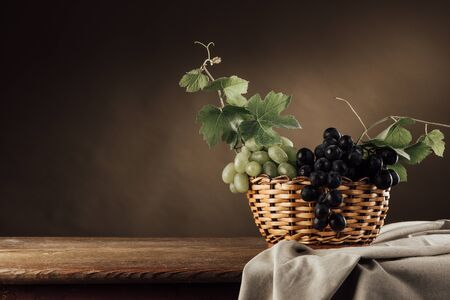 fruit basket: Seasonal ripe grapes in a basket on a rustic wooden table, vine leaves and drape, classic still life Stock Photo
