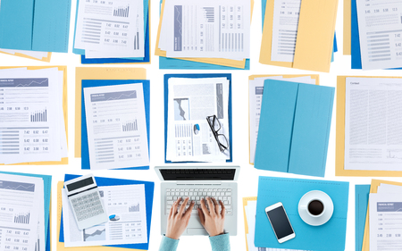 financial reports: Business woman working at desktop on a laptop with financial reports, paperwork and files, top view, unrecognizable person Stock Photo
