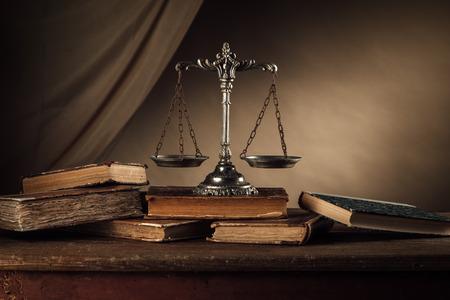 古い銀のスケールと木製のテーブル、正義および知識概念にハードカバーの本 写真素材