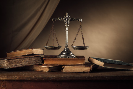 Escala y de libros de tapa dura de plata viejos en una mesa de madera, la justicia y el concepto de conocimiento