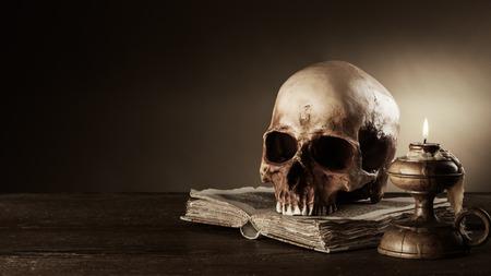 Menselijke schedel, kaarsen verlicht en een open oude boek op een oude houten tafel, kennis en begrip geletterdheid