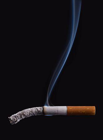 bad habit: Cigarette burning on dark black background with smoke, stop smoking concept