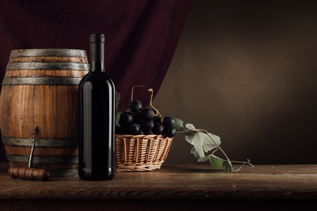 wine barrel: Red wine bottle, barrel and basket with grapes on a rustic wooden table, red drape on background, wine tasting still life