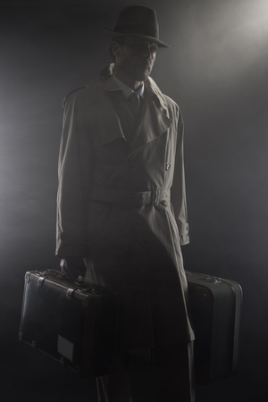 undercover agent: Man in trench coat with hat and luggage leaving in the dark, 1950s style film noir
