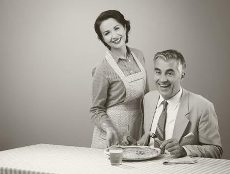Esposas: Feliz de la vendimia pareja cenando, ella está sirviendo una pizza a su marido