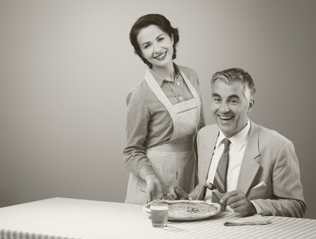 wife and husband: Happy vintage couple having dinner, she is serving a pizza to her husband