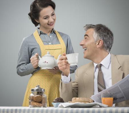 ama de casa: 1950 hermosa mujer servir el t� para el desayuno a su marido sonriente Foto de archivo