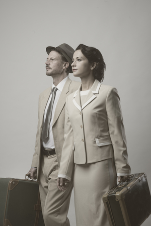 old fashioned: Elegant vintage couple walking and holding suitcases, travel concept