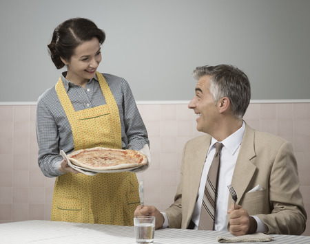dinner: Happy vintage couple having dinner, she is serving a pizza to her husband