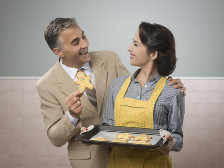 taking a wife: Vintage woman serving home made gingerbread men cookies to her smiling husband