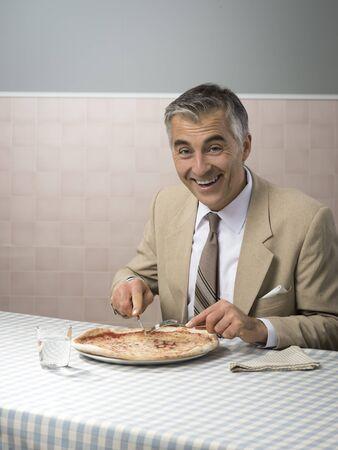 pause repas: Smiling elegant businessman having a pizza during his lunch break Banque d'images