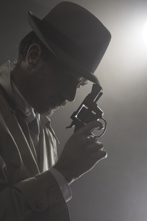 Handsome detective in trench coat holding a gun in the dark, film noir Foto de archivo