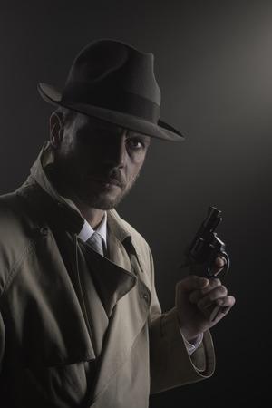 hombre con sombrero: Detective hermoso en gabardina con una pistola en la oscuridad, el cine negro