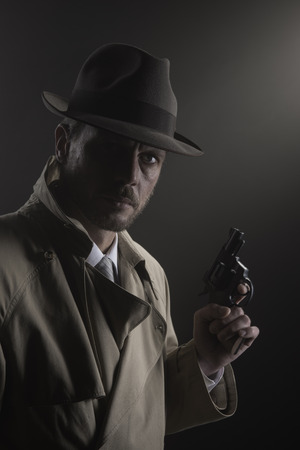 fedora hat: Handsome detective in trench coat holding a gun in the dark, film noir Stock Photo