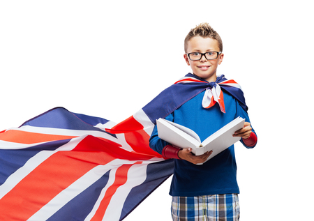 Cute superhero boy reading a book, he is wearing a British flag as a cape, education and enjoyment concept Banque d'images
